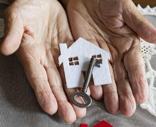 elder hands holding a house key