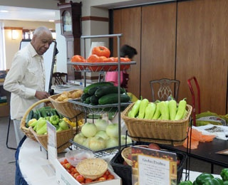 man looking at fresh vegetables on a table