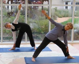2 older adult women doing yoga