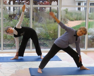 2 older adult women doing yoga