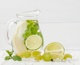 pitcher of water with lime slices and green grapes