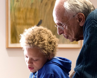 older adult man helping a young boy