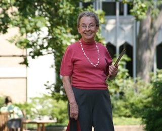 older adult woman on a campus holding folders