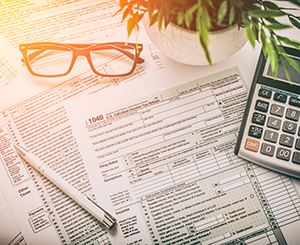 Tax forms lying on the desk with glasses and calculator.