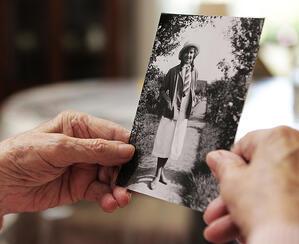 Older woman holding up an old photograph reflecting on her life while downsizing
