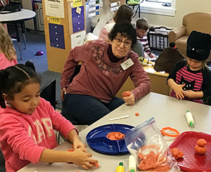 Betsy M with children - for blogKendal resident and early learning center children