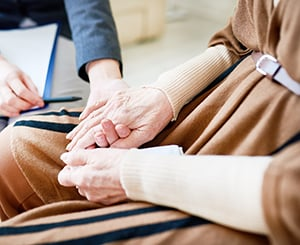 A woman supporting an older adult who is coping with grief