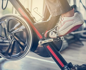 Older adult cycling at the gym to stay healthy