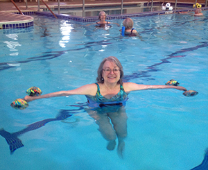 Older woman swimming in the pool to keep her heart in shape.
