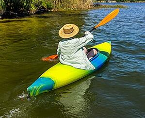 Senior woman kayaking down a river.