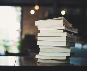 Books stacked on each other on a table in a cafe.