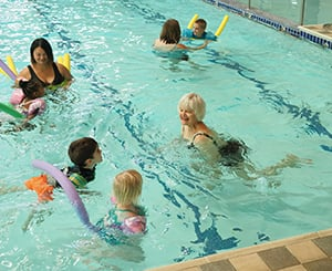 Group of residents and children swimming in community pool.