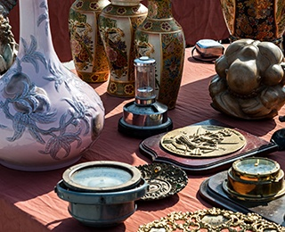 Antiques and memorabilia set out on a table at a garage sale.