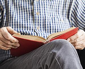 Older adult man enjoying a good book.