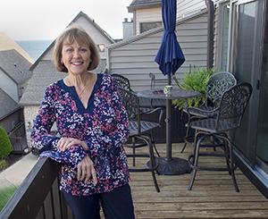 maggie standing on balcony after downsizing home
