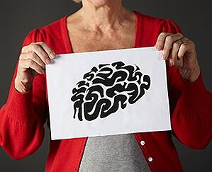 Senior woman holding an ink drawing of a brain.