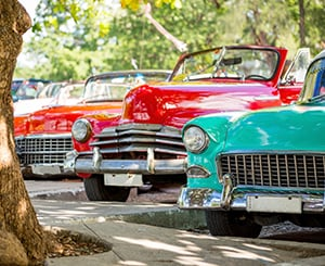 Classic cars sitting alongside a road during car show